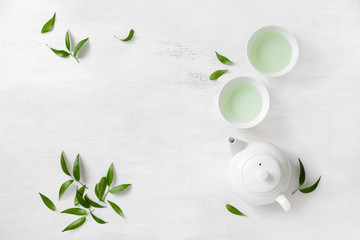 Two white cups of tea and teapot, top view background