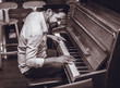 Trendy man with stylish hat and beard trying playing vintage old wooden piano