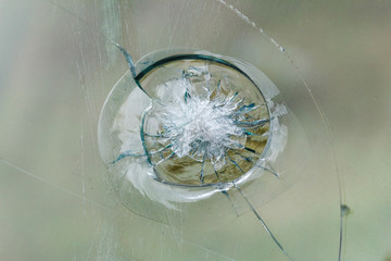 Firearms bullethole on bulletproof glass, cracks background