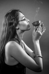 Sorcery, Tribute and prayer. Beautiful brunette with bronze bowl and incense in a gesture of faith
