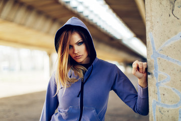 Portrait of a young beautiful woman in a hoodie in an urban environment
