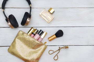 Accessories, Cosmetics, headphones shiny lie on a wooden background. View from above