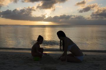 夕暮れの海で遊ぶ親子