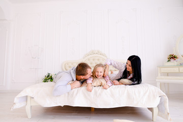 Wife, husband and daughter hugging and smiling portrait of famil