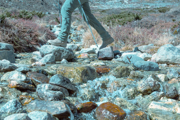 Clean Mountain Creek and Hiker crossing it trendy toned