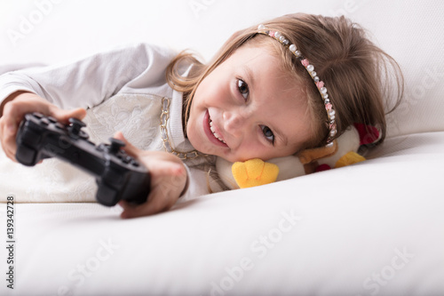 quotsmiling pretty little girl playing video gamesquot stock