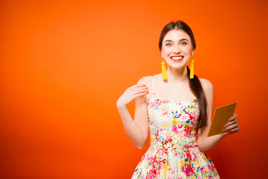 Beautiful smiling woman with mail envelope. Over orange background