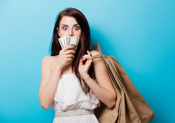 beautiful young woman with shopping bags and money standing in front of wonderful blue background