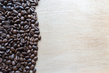 Coffee beans on wooden table texture with copy space