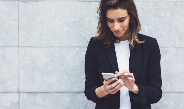Portrait young businesswomen in black suit using smartphone isolated on background concrete gray wall mockup, pretty hipster manager holding mobile gadget, girl smiletexting message, connect