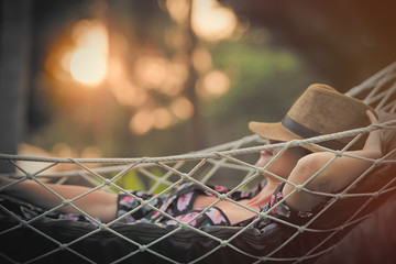 beautiful young woman lying in a hammock and relaxing with hat on her head Wall mural