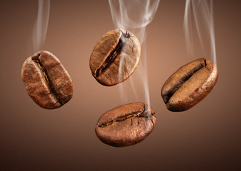 Closeup falling coffee beans with smoke on brown background