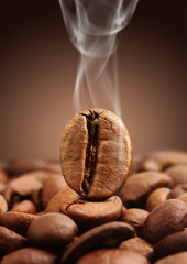 Macro coffee bean with smoke on brown background
