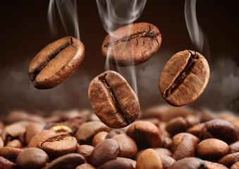 Closeup falling coffee bean with smoke on brown background