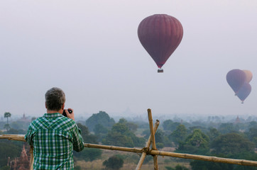 tourist take picture of sunrise with balloons in Bagan.