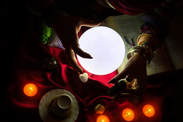 Top view on crystal ball and hands of fortune teller