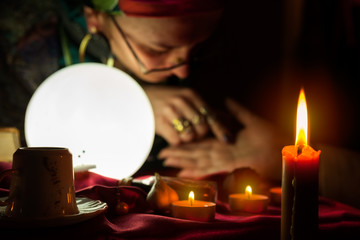 Burning candle and fortune teller who read a fortune from palm