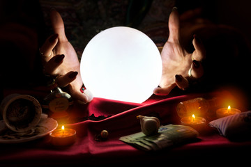 Hands of fortune teller with crystal ball in the middle