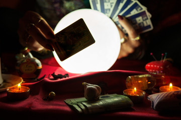 Tarot card and crystal ball behind it