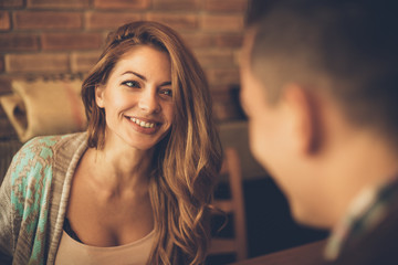 Young woman has a big smile while looking at a man at a table in a cafe