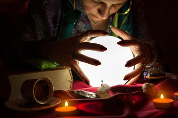 Gypsy fortune teller woman with her hands above crystal ball