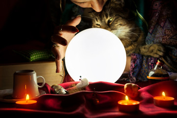 Glowing crystal ball with gypsy fortune teller who holds a cat