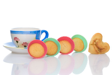 Cup of tea with a heart cake and silicon baking dishes. White background.