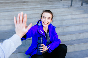 First person view of a man and woman high fiving. Happy young woman in blue sportswear sitting on a stairs and giving high five to man after outdoor training.