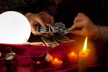 Tarot cards in hands of old gypsy fortune teller