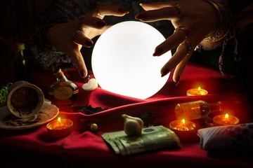 Hands from fortune teller above crystal ball
