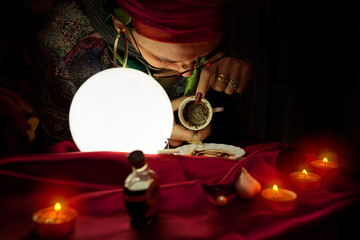 Gypsy clairvoyant woman reads a fortune from empty coffee cup