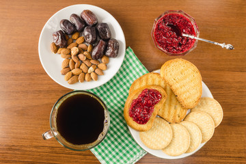 Breakfast time, cup of coffee with toasts, raspberry jam, dates, almonds on wooden table, top view.