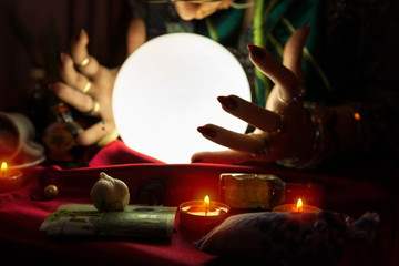 Illuminated crystal ball and hands of fortune teller woman