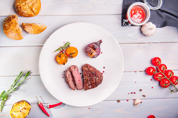 Top view Grilled beef tenderloin steak with grilled onion and cherry tomatoes on the white plate on the wooden background with details. Selective focus