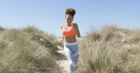 Horizontal outdoors shot of young woman jogging on Tarifa beach in lovely sunny day in Cadiz, Spain.