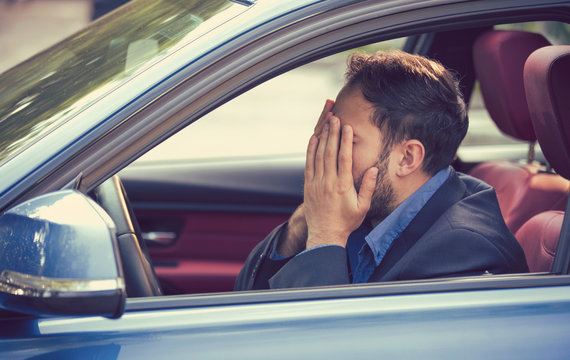 man sitting inside his car and feeling stressed and upset