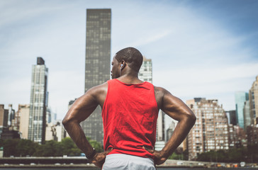 Urban runner looking New york skyline while taking a break