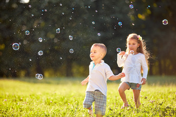 Young boy and girl looking at soap bubbles