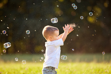 Kid in nature reaching soap bubbles
