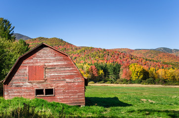 Disused Red Barn in a Grassy Field with Colourful Forested Mountains in Background