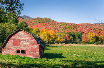 Disused Old Red Barn with Forested Mountains in Background on a Clear Autumn Day. Beautiful Autumn Colours.