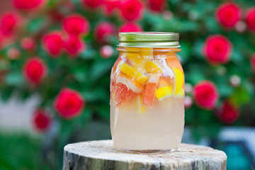Fresh lemonade from lemon and grapefruit and orange in a jar on a wooden stump.