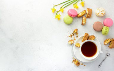 Cup of black tea with tasty almond cookies rich in vitamins minerals varicolored macaroons and flowers on a white background in light key. Top view copy space.