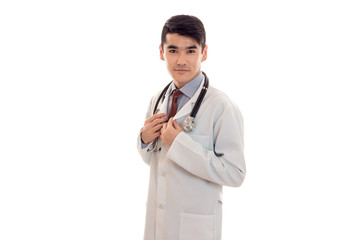 a young doctor in a white lab coat with a stethoscope looks at camera