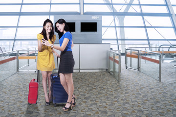 Attractive girls with cellphone in airport