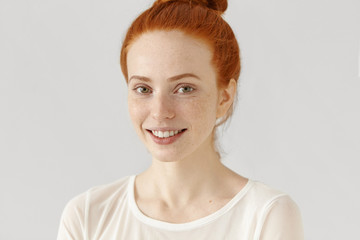 Half profile of beautiful redhead girl with healthy freckled skin and hair bun smiling cheerfully at camera while posing isolated against white blank wall background with copy space for your content