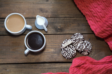 Cup of black coffee, cup of coffee with milk, cream. Pink woven scarf. Marshmallow with chocolate. Dark wooden background. Beautiful vintage coffee groundwork. Coloring and processing photo.