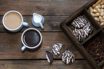 Cup of black coffee, cup of coffee with milk, cream. Marshmallow with chocolate, peanut and coffee beans in box. Dark wooden background. Beautiful vintage coffee groundwork. Coloring photo.