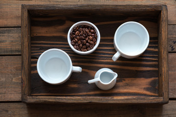 Two white cup, cream and coffee beans in box. Dark wooden background. Beautiful vintage coffee groundwork. Coloring and processing photo.