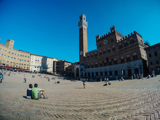 People sitting at historical old town square in Siena, Tuscany, Italy
